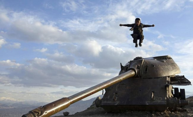 An Afghan boy jumps off the turret of a Soviet tank on a hilltop on the the outskirts of Kabul, ...
