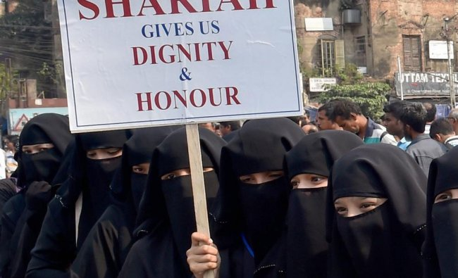 Muslim women hold posters and participate in a silent rally demanding taking back of Triple Talaq..