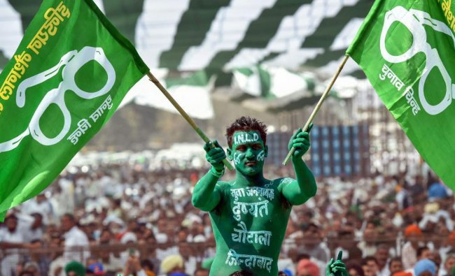 An Indian National Lok Dal (INLD) supporter waves party flags during farmers\' rally at Ramlila...