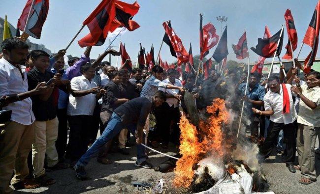 DMK members, along with the members of various Tamil outfits, burn an effigy of BJP leader H Raja...