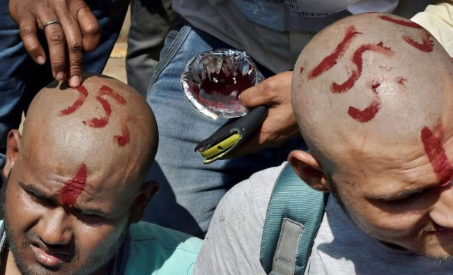 Staff Selection Commission (SSC) aspirants get their heads tonsured during a protest over the...