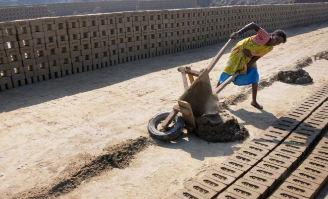 A woman works at a brick field in a village on the the outskirts of Amritsar on Wednesday, a day...