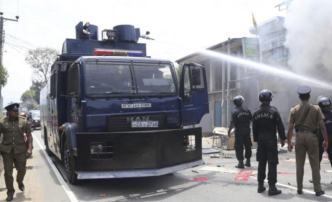 Sri Lankan police officers attempt to douse burning shops in Ambatenna, in central Sri Lanka...