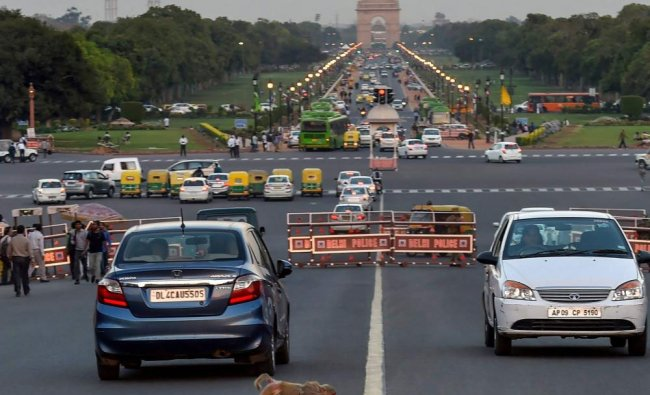 A monkey crosses a road near Vijay Chowk as India Gate is also seen in the background, in ...