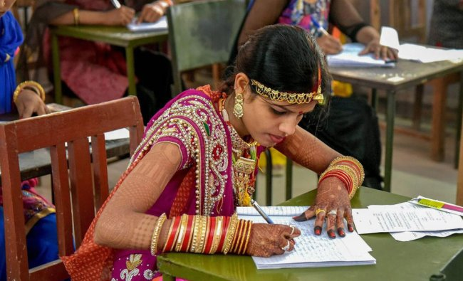 Newly married Aruna Prajapat writes her BA examination paper in Bikaner on Friday, a day after...
