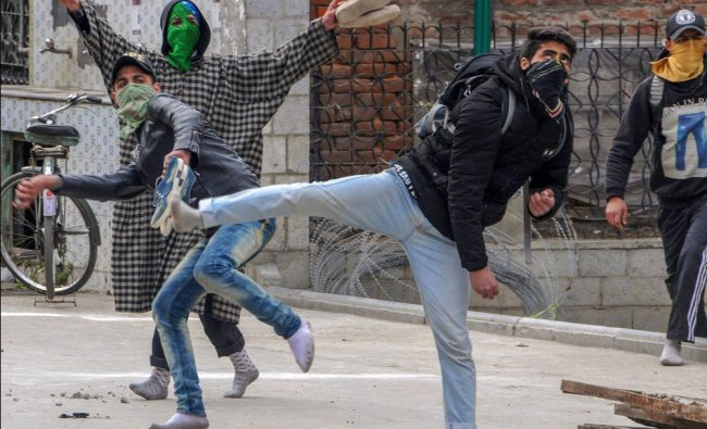 Youth throw stones at police personnel during clashes between police and protesters, over the...