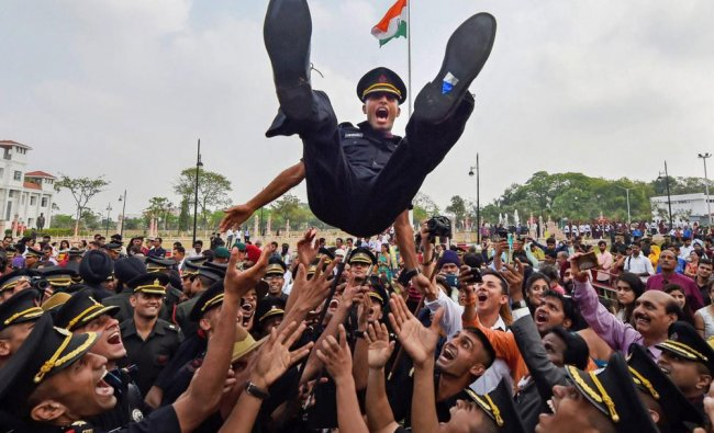 Cadets lift a colleague as they celebrate after a passing-out parade at Officers Training...