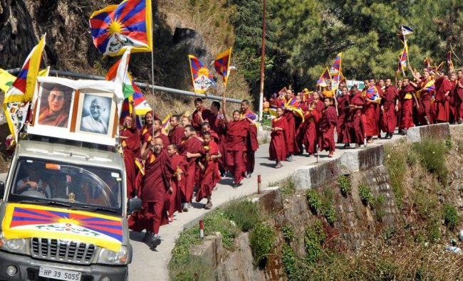 Tibetans, living-in-exile in India, raise slogans at an event to mark the 59th Tibetan...