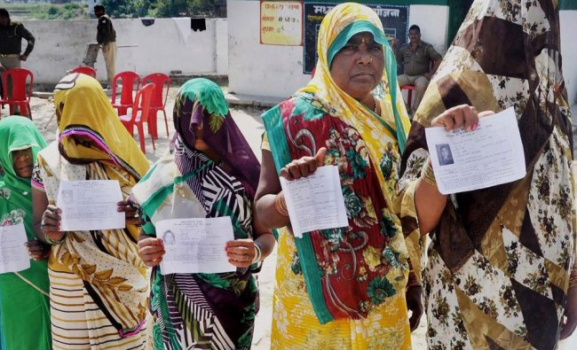Voters display their voter\'s ID card at a polling booth for Phulpur bypoll elections...