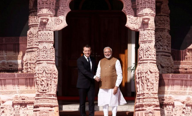 Prime Minister Narendra Modi (R) shakes hands with French President Emmanuel Macron...