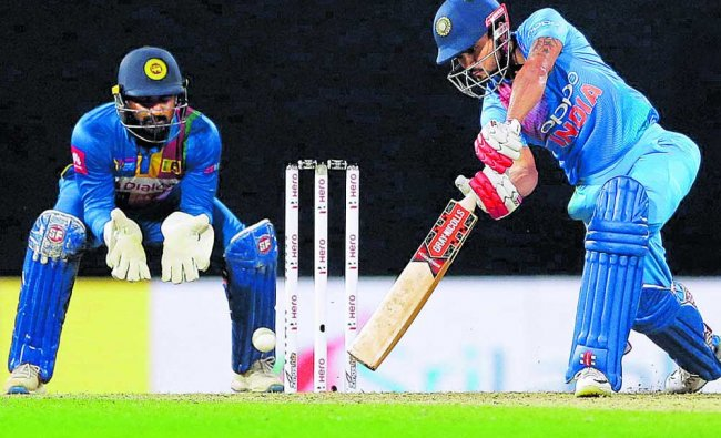 India\'s Manish Pandey plays a shot as Sri Lanka\'s Kusal Perera watches during their Twenty20...