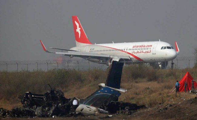 A plane lands near the crash site, a day after the US-Bangla airplane crashed while arriving...