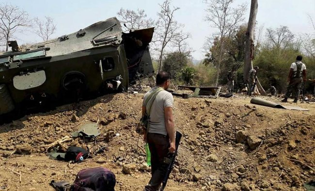 Security personnel inspect the site of an IED blast where nine CRPF personnel were killed...