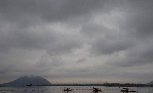 Kashmiri boat persons row their shikara as dark clouds gather during rains...