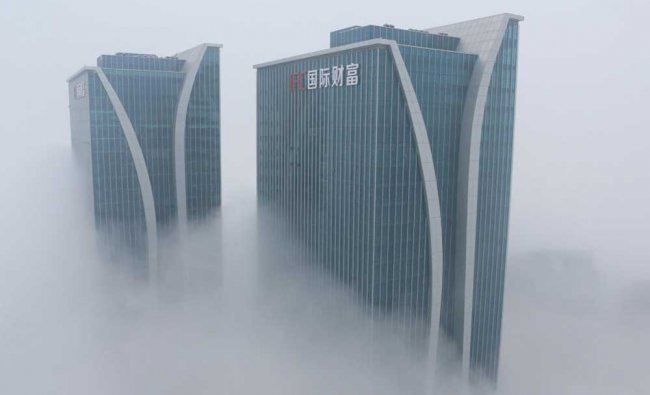 Buildings are seen among fog in Rizhao, Shandong...