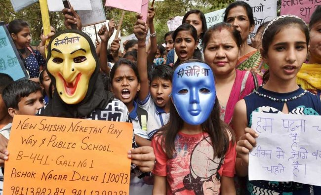 Students and teachers wearing masks display placards during a protest against the Delhi...