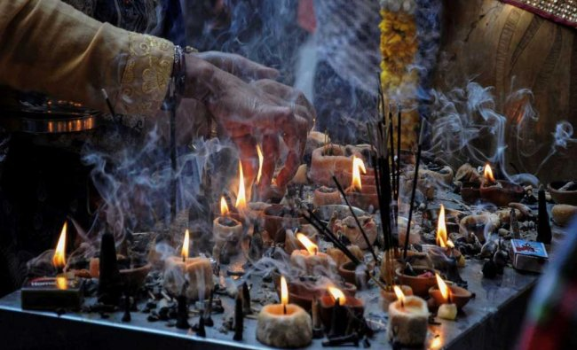 A Hindu devotee places an incense stick at a temple on the occasion of Navratri festival...