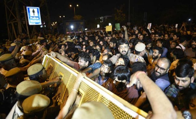 Security personnel stop JNU students during their protest against JNU professor who is accused...