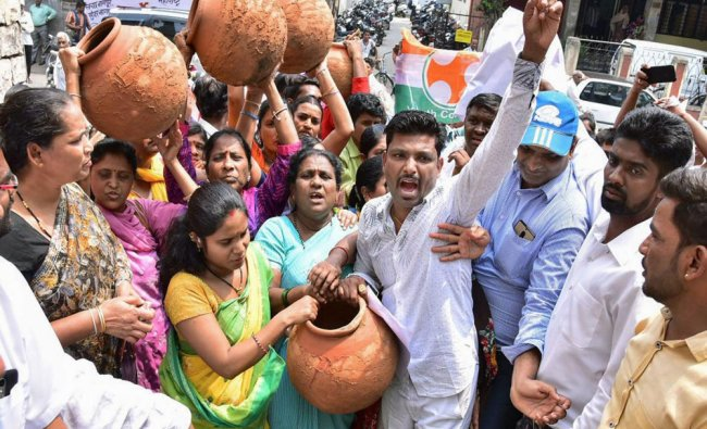 Youth Congress supporters demonstrate with earthen pots during a protest against shortage...