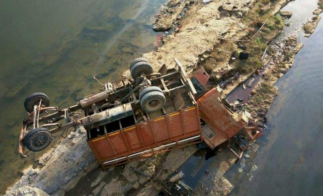 The mangled remains of a mini-truck carrying a marriage party which fell from a bridge is seen lying into the dry Son riverbed near Amelia village in Sidhi District of Madhya Pradesh on Wednesday. At least 22 people were killed and many others suffered serious injuries in the accident. PTI