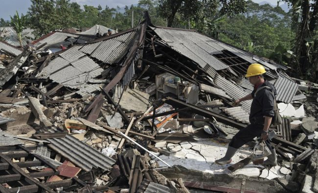 A rescuer walks on the rubble of houses in an area affected by an earthquake in Kalibening, Central Java, Indonesia, Thursday, April 19, 2018. The shallow earthquake in central Indonesia has killed people and damaged hundreds of homes, disaster officials said Thursday as they declared a two-week emergency for the affected areas. AP/PTI