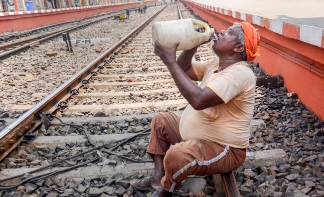 A worker drinks water from a big plastic jar on a hot sunny day at Barnagar railway station in Kolkata on Friday. PTI Photo