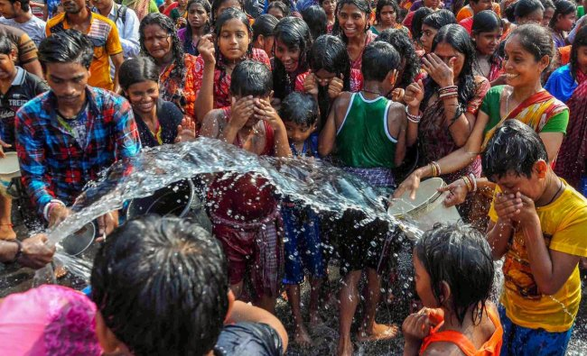 A man shower water on the devotees to cool them during \'Dandi\' rituals as part of \'Goddess Shitala Puja\' in Kolkata on Saturday. PTI Photo
