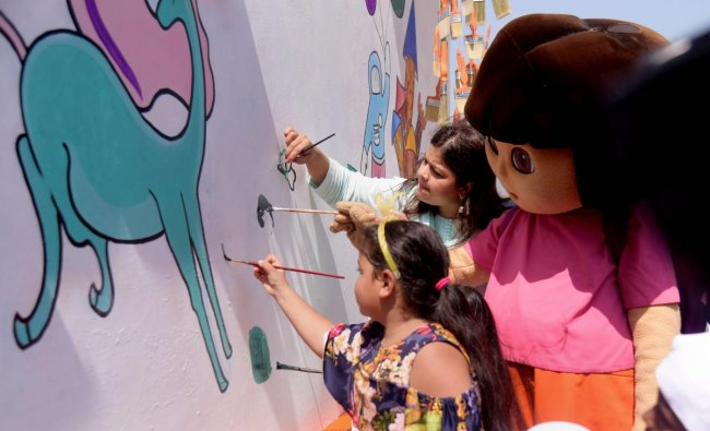 BJP leader Poonam Mahajan, Nicktoon Dora and and kids paint a wall as part of a campaign to beautify the city, in Mumbai on Saturday. PTI Photo