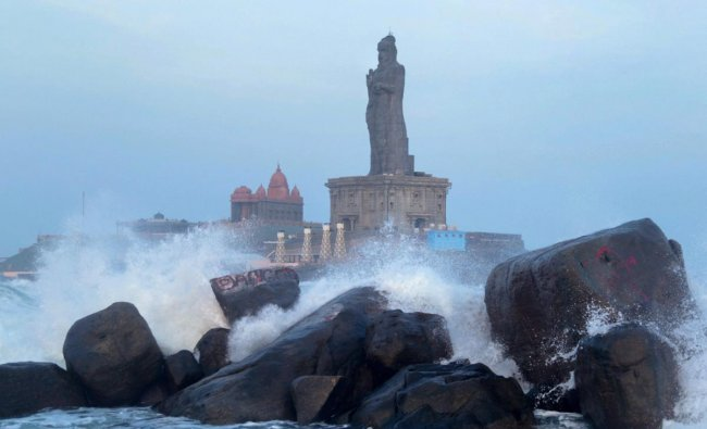 High waves hit the rocks around the Thiruvalluvar Statue in Kanyakumari on Sunday. Ferry services to Thiruvalluvar were temporarily suspended following Met department\'s announcement that high tidal waves were set to hit the coast. PTI Photo