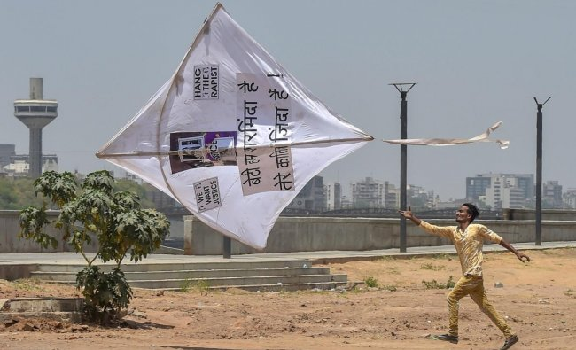 A man runs after a kite during a protest against the recent rape and murder of an eight-year-old Kathua girl, an Unnao teenager and an eleven-year-old Surat girl, in Ahmedabad on Sunday. PTI Photo