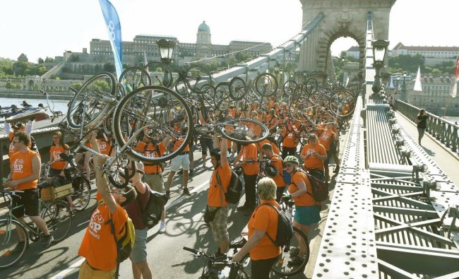 Cyclists raise their bikes on Chain Bridge across River Danube with the Royal Palace in the background during a march called I Bike Budapest in Budapest, Hungary. AP/PTI Photo