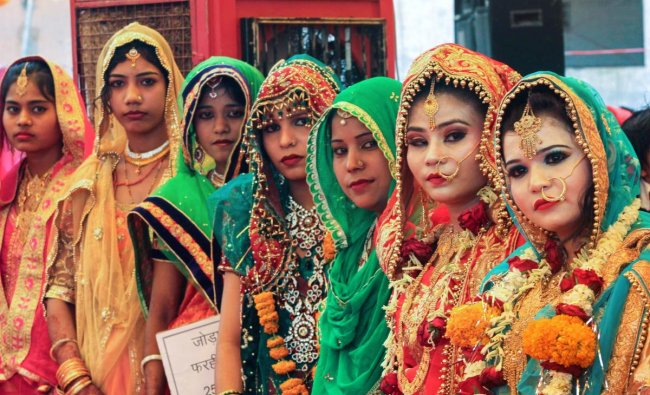 Brides pose for a photograph during a mass marriage ceremony under Mukhyamanti Kanyadan Yojna in Bhopal on Wednesday. More than 65 couples tied the knot. PTI Photo