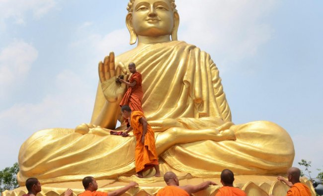 Buddhists monks clean a statue of Lord Buddha ahead of Buddha Purnima festival in Howrah on Wednesday. PTI Photo