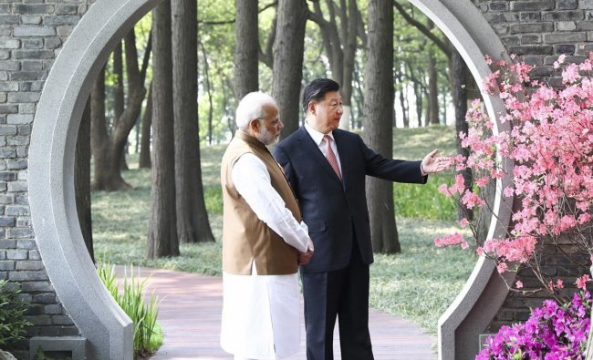 In this photo released by China\'s Xinhua News Agency, Indian Prime Minister Narendra Modi, left, and Chinese President Xi Jinping talk at a garden in Wuhan in central China\'s Hubei Province, Saturday, April 28, 2018. The leaders of China and India stressed the importance of close ties in talks Saturday, against the background of their rivalry for leadership in Asia and the potential for cooperation on economic and security matters. (AP/PTI)