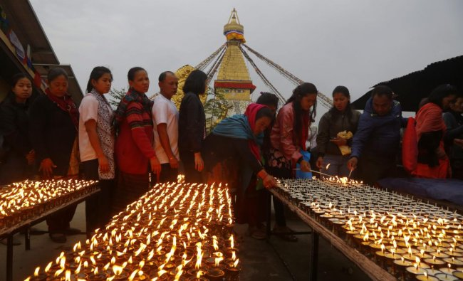 Nepalese Buddhist devotees line up in a queue to light butter lamps in a monastery during Buddha Jayanti or Buddha Purnima in Boudhanath stupa, Kathmandu, Nepal. AP/PTI Photo