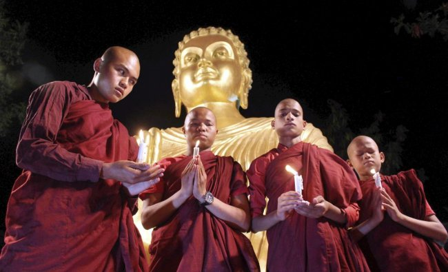 Buddhist monks offering prayers at the statue of Lord Buddha on the eve of Buddha Purnima in Bhopal. PTI Photo