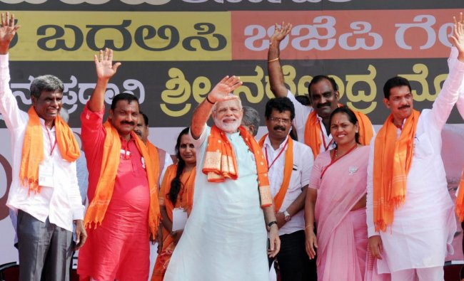 Prime minister Narendra Modi, along with the BJP leaders, waves at the crowd at an election campaign rally in Udupi on Tuesday, ahead of Karnataka polls. PTI Photo