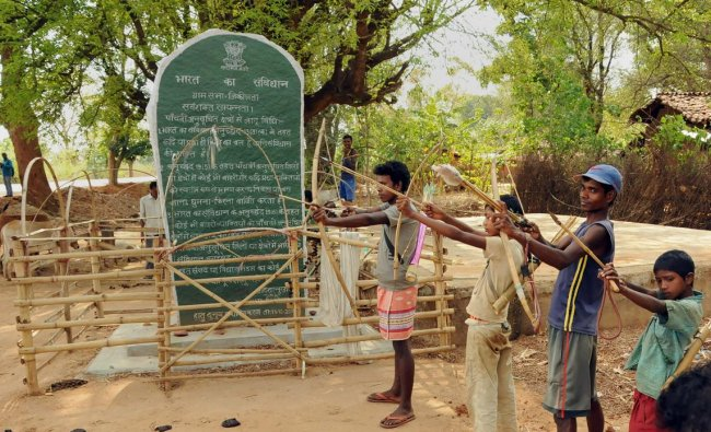"""Tribals hold bows and arrows near a Patthalgarhi spot at Maoist-affected village Siladon under Khunti district of Jharkhand on Tuesday. The Patthalgarhi movement says that the """"gram sabha"""" has more weight than either the Lok Sabha or the Vidhan Sabha in scheduled areas. PTI Photo"""