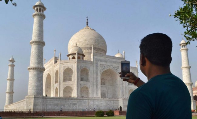 A man clicks picture of Taj Mahal in Agra on Tuesday. The Supreme Court on Tuesday expressed concern over the change of colour of the iconic Taj Mahal which had become yellowish earlier and was now turning brown and green. PTI Photo