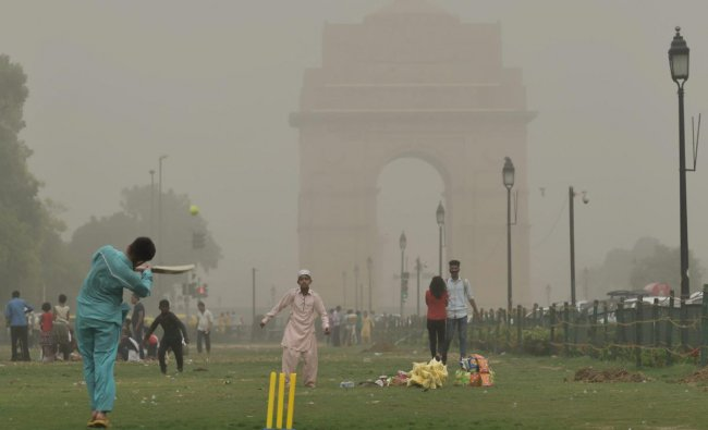 Children play cricket as the weather changes during a after dust storm in New Delhi on Wednesday. PTI Photo