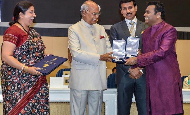President Ram Nath Kovind confers Best Music Direction Award on AR Rahman during the 65th National Film Awards function at Vigyan Bhavan in New Delhi on Thursday. I & B Minister Smriti Irani and MoS for I & B Rajyavardhan Rathore are also seen. PTI Photo