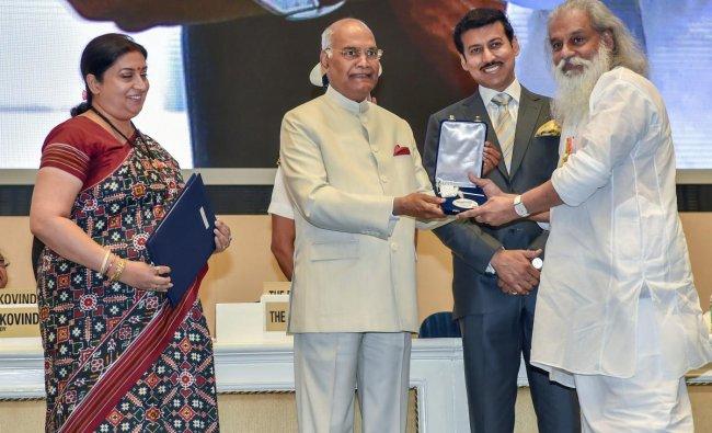 President Ram Nath Kovind confers Best Playback Singer Award on K J Yesudas during the 65th National Film Awards function at Vigyan Bhavan in New Delhi on Thursday. I & B Minister Smriti Irani and MoS for I & B Rajyavardhan Rathore are also seen. PTI Photo