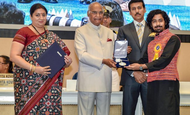 President Ram Nath Kovind confers Best Actor Award on Riddhi Sen during the 65th National Film Awards function at Vigyan Bhavan in New Delhi on Thursday. I & B MInister Smriti Irani and MoS for I & B Rajyavardhan Rathore are also seen. PTI Photo