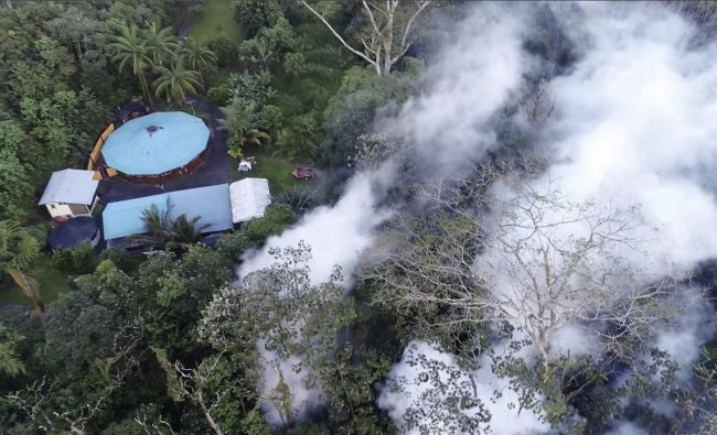 In this still frame taken from video, lava flows toward a home in the Puna District as a result of the eruption from Kilauea Volcano on Hawaii\'s Big Island, Friday, May 4, 2018. The eruption sent molten lava through forests and bubbling up from paved streets and forced the evacuation of about 1,500 people who were still out of their homes Friday after Thursday\'s eruption. AP/ PTI
