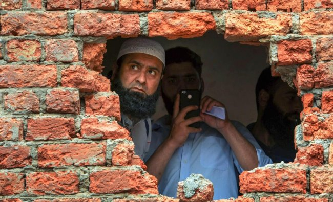 A man looking out from a hole of a house which was damaged during encounter between security forces and militants at Chatabal in Srinagar, on Saturday. Three militants and civilian were killed in the gunbattle. PTI
