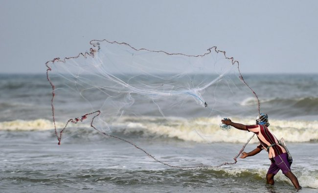 A fisherman throws a net for fishing at Marina Beach in Chennai on Saturday. PTI