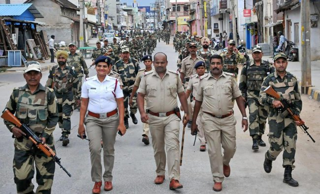 Security personnel march ahead of Karnataka assembley elections at Chikmagalur in Karnataka on Sunday. PTI