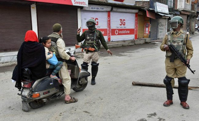 A security personnel stops a scootrist during curfew-like restrictions imposed to maintain law and order in Srinagar on Monday. A strike call was given by the separatists over the recent killings of civilian. PTI