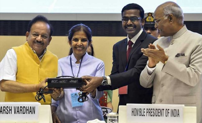 Minister for Science and Technology Harsh Vardhan launches the \'Product of the Year 2018: Charger for the Lithium Ion Battery\' by M/s Ampere Vehicles, Coimbatore, during the inauguration of the 20th National Technology Day 2018 function in New Delhi on Friday. President Ram Nath Kovind is also seen. PTI