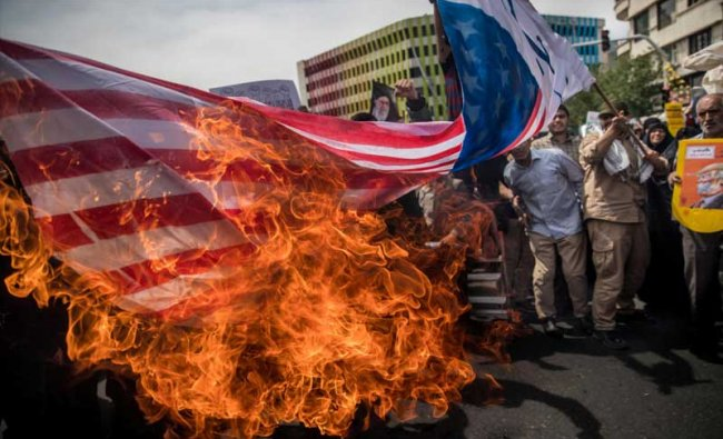 Iranians burn a U.S. flag during a protest against President Donald Trump\'s decision to walk out of a 2015 nuclear deal, in Tehran, Iran, May 11, 2018. REUTERS/Tasnim News Agency